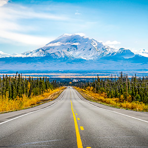 Alaska road with mountain and blue sky